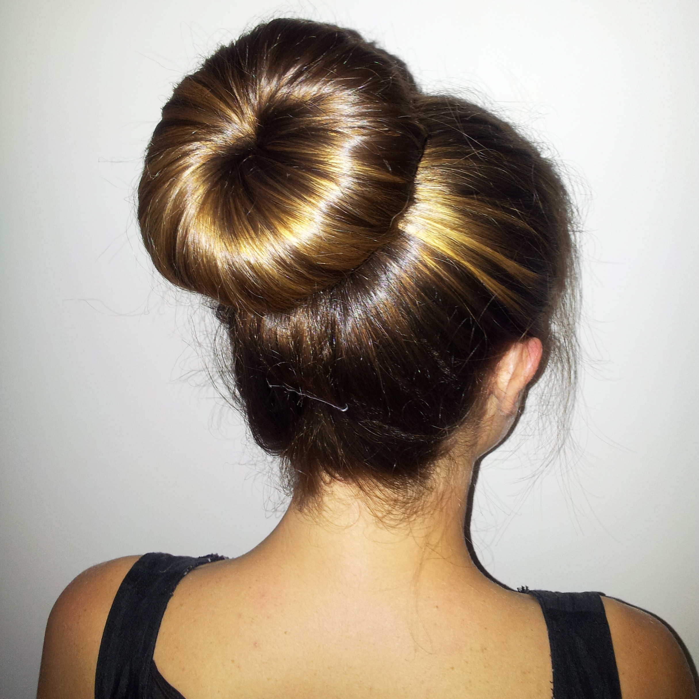 Wrap and twist your hair around the ring to create a bun shape. Spread your hair down and around the ring, until you've covered the entire doughnut with hair.